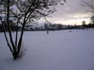 A lone walker in a snowy park