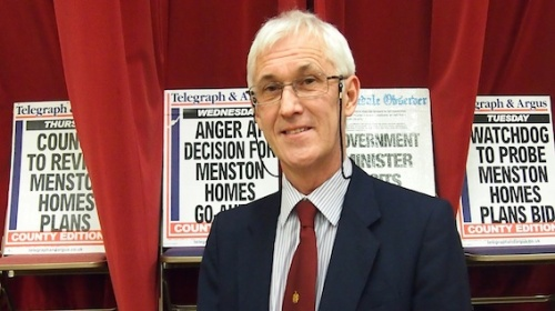 Dr Ellams pictured in front of local newspaper placards announcing campaigns against inappropriate development in Menston