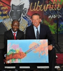 David Geldart presenting Minister Counsellor, Dumisani Ntuli with a painting from one of St Mary's students, Sara Riley, which symbolises the work of the Bambisanani Partnership,at a Leeds Civic Reception to celebrate the 'Life and Legacy' of Nelson Mandela