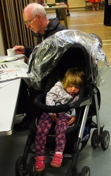 Mite in pushchair sleeping while grandad has a cup of tea