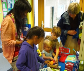 Children and adult helpers in the mini toy supermarket set up by Cleasby Kindercare in the MBA youngster's zone