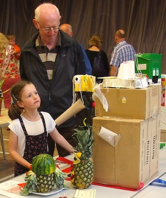 Little girl admires the robots made for the children's handicrafts class