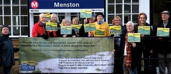 Some of the MAG members and other Menston residents at Menston Station on their way to the Leeds High Court where MAG is seeking a Judicial Review. They are displaying the poster warning potential house purchasers of the flood risk should houses be built on the proposed Derry Hill and Bingley Road sites