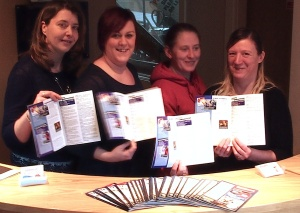 The team which has brought a new community magazine to Menston. Left to Right: Louise Atkinson, partner and graphic designer, Cathy Frobisher , Office Manager, Janet-Alison Arkwright , Partner and 'Sales Contributor', and Andrea Kerman, Sales Person, at the reception in their offices in Haworth, each holding the first edition of the new magazine.