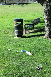The seat and litter bin near to the ugly building with Easter Monday morning rubbish on the ground