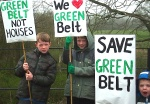 Three young protesters with their green belt messages on placards