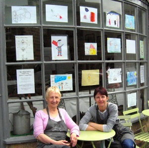 Owner of the Village Bakery Trish and helper Sue (from Bleach Mill House) outside the bakery with the entries to the shop's Fathers' Day competition on display in the window