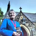 Sheila Glennie with her medal outside Menston Parish Church