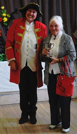 Carol Baldam with Barnoldswick Town Crier. Carol is holding Menston Show Handicrafts Cup which she won