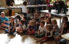 Children sitting on the floor at the front, eagerly awaiting the prize giving