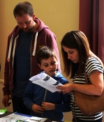 Mum, dad and son consult the listing of classes near the Rio Olympics art entries