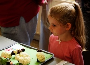 Young girl looking at the sheep models made from cauliflower and olives