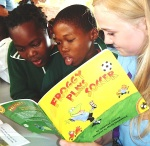 Photo of St Mary's student reading with two South African pupils during a Bambisanani project visit to South Africa